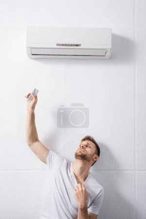 sad man feeling uncomfortable with broken air conditioner at home during summer heat