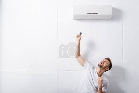 confused man holding remote controller and suffering from heat with broken air conditioner at home