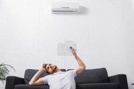 Photo pour Homme frustré tenant télécommande et souffrant de chaleur avec climatiseur cassé à la maison - image libre de droit