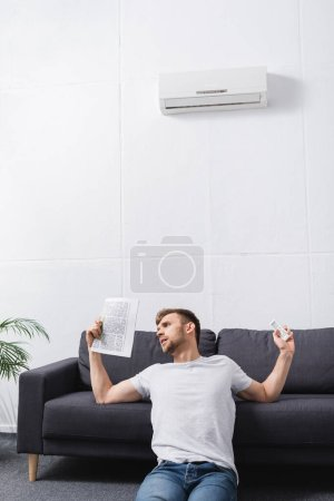 sad young man suffering from heat while using newspaper as hand fan at home with broken air conditioner
