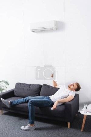 exhausted man suffering from heat while using newspaper as hand fan at home with broken air conditioner