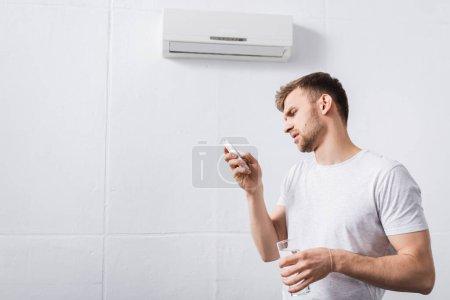 Photo pour Homme frustré tenant verre d'eau tout en essayant d'allumer le climatiseur avec télécommande cassée à la maison - image libre de droit