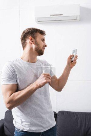 Photo pour Triste homme tenant verre d'eau tout en essayant d'allumer le climatiseur avec télécommande cassée à la maison - image libre de droit