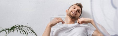 positive emotional man feeling comfortable with electric fan at home during summer heat, panoramic crop