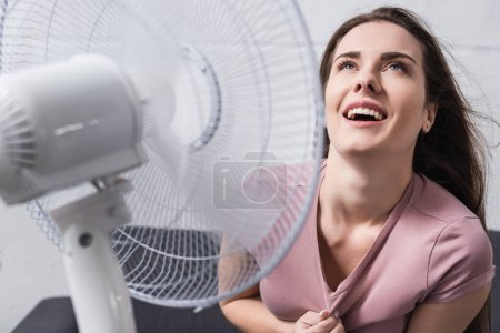 Photo for Excited woman feeling comfortable with electric fan at home during summer heat - Royalty Free Image