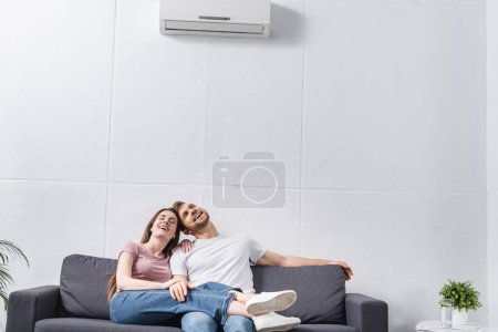 Photo for Happy emotional couple at home with air conditioner - Royalty Free Image
