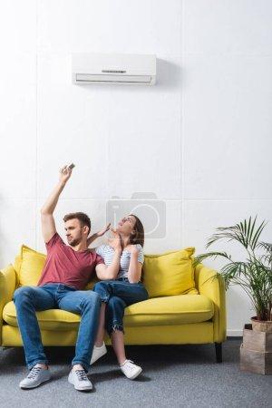 Photo pour Couple bouleversé avec télécommande souffrant de chaleur à la maison avec climatiseur cassé - image libre de droit