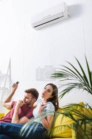Photo pour Couple bouleversé assis à la maison avec climatiseur cassé - image libre de droit