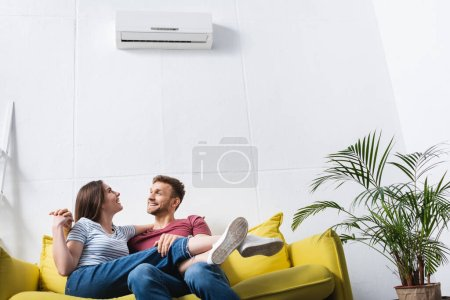 Photo for Happy young couple hugging at home with air conditioner - Royalty Free Image