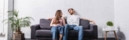 Photo pour Jeune couple épuisé souffrant de chaleur tout en étant assis à la maison avec climatiseur cassé, en-tête de site Web - image libre de droit