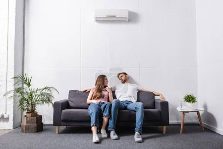 Photo for Young couple suffering from heat while sitting home with broken air conditioner - Royalty Free Image