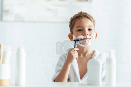 Photo for Selective focus of cute boy shaving in bathroom near toiletries - Royalty Free Image