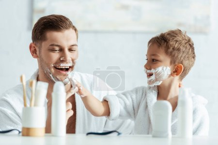 selective focus of smiling boy applying shaving foam on face of cheerful father