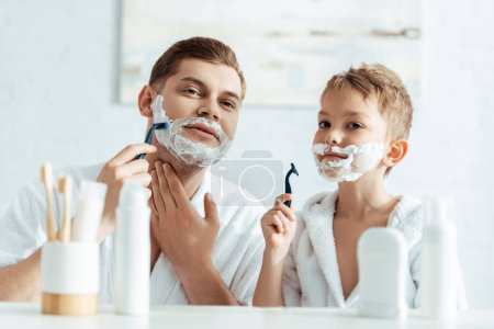 selective focus of father and son shaving in bathroom together