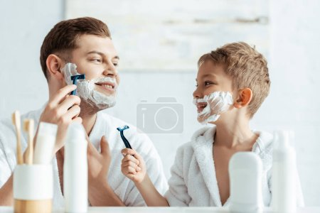 selective focus of smiling boy with foam on face looking at shaving father