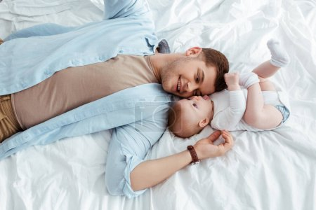 Photo for Top view of smiling young father lying face to face with cute little son in bed - Royalty Free Image