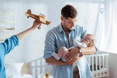 Photo pour Vue partielle du garçon tenant l'avion jouet près du père tenant le petit frère mignon - image libre de droit