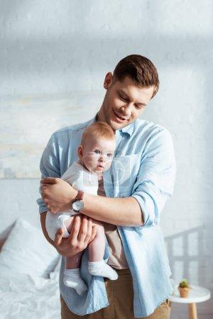 Photo pour Heureux père tenant adorable bébé sur les mains dans la chambre - image libre de droit