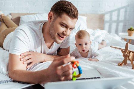 Photo pour Foyer sélectif du père souriant montrant bébé hochet à mignon petit fils tout en étant couché sur le lit près d'un ordinateur portable - image libre de droit