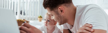 Photo for Panoramic shot of young father and cute little son on bed near laptop - Royalty Free Image