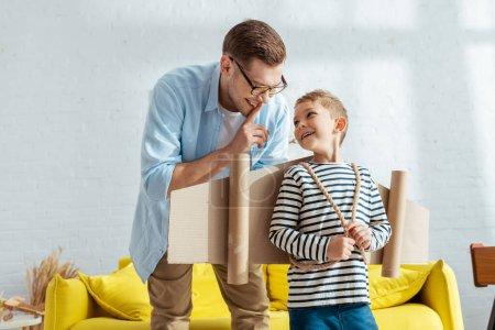 Photo pour Joyeux père montrant un geste de silence au fils heureux avec des ailes en carton derrière le dos - image libre de droit
