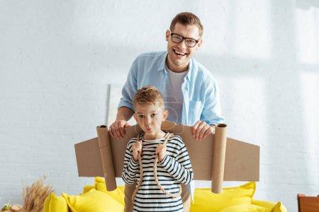 Photo pour Heureux père et adorable garçon avec des ailes de carton sur le dos regardant caméra - image libre de droit