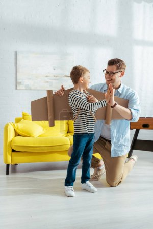 smiling father giving high five to happy son with carton wings on back