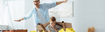 Photo for Panoramic concept of happy boy with carton plane wings, and cheerful father having fun while imitating flying - Royalty Free Image