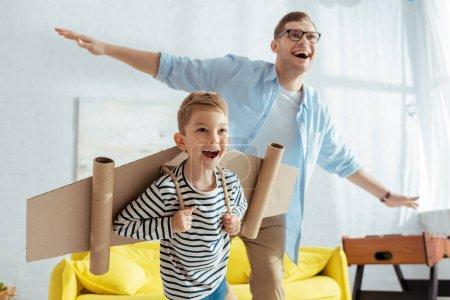 Photo pour Garçon heureux avec des ailes d'avion de carton, et père joyeux s'amusant tout en imitant voler - image libre de droit