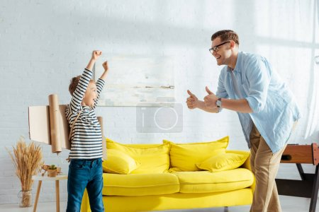 happy boy with carton plane wings on back showing yeah gesture near father showing thumbs up