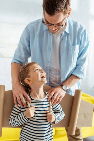 smiling father touching shoulders of happy son with cardboard plane wings on back