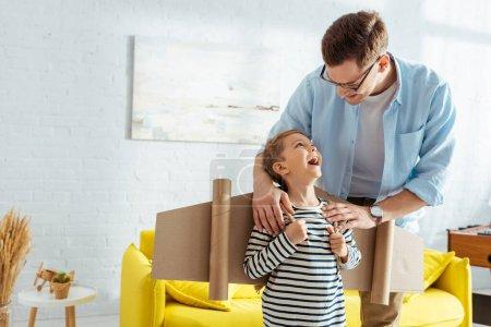 Photo pour Le père souriant touchant les épaules d'adorable fils avec des ailes d'avion en carton sur le dos - image libre de droit