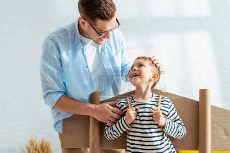 Foto de Padre feliz tocando la cabeza del hijo alegre con alas de avión de cartón en la espalda - Imagen libre de derechos