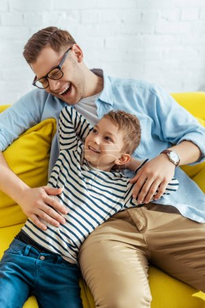 Photo for Happy father and son laughing while sitting together at home - Royalty Free Image
