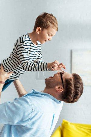 Photo pour Adorable garçon montrant geste effrayant au père le tenant sur les mains au-dessus de la tête - image libre de droit
