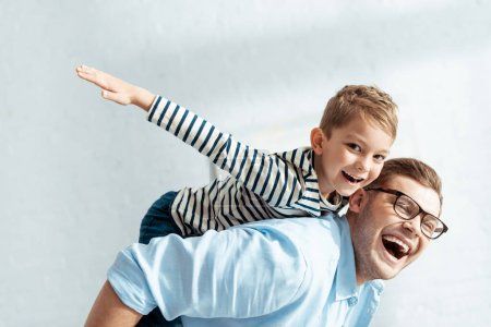 cheerful father piggybacking happy son looking at camera and imitating flying