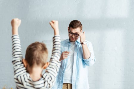 back view of boy showing winner gesture near father touching forehead