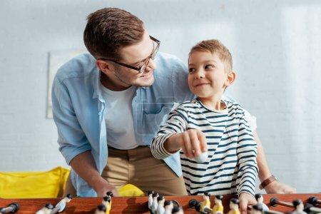 Photo pour Heureux père et fils regardant l'autre tout en jouant au baby-foot - image libre de droit