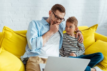 Photo for Young father laughing and hugging son while sitting on sofa and using laptop - Royalty Free Image