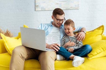 Photo pour Excité père et fils riant tout en étant assis sur un canapé jaune avec ordinateur portable - image libre de droit