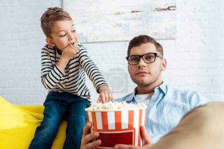 Photo pour Mignon garçon prendre pop-corn de seau tandis que concentré père regarder la télévision - image libre de droit