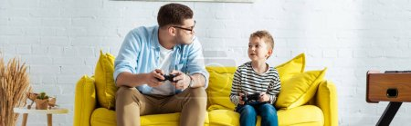 Photo for KYIV, UKRAINE - JUNE 9, 2020: horizontal image of young father and cute son sitting on yellow sofa with joysticks - Royalty Free Image