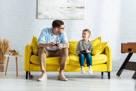 KIEW, UKRAINE - 9. JUNI 2020: Junger Vater und entzückender Sohn schauen sich auf gelbem Sofa mit Joysticks an