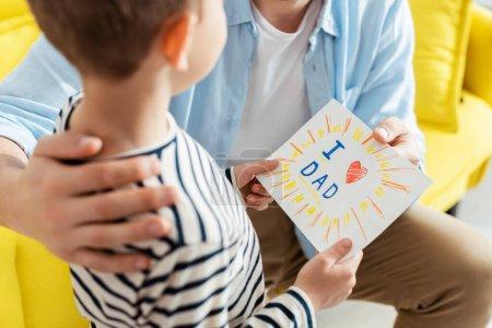 Foto de Vistas rotas del padre abrazando al hijo presentándole a los padres hechos a mano tarjeta de felicitación el día de los padres con letras y símbolo del corazón. - Imagen libre de derechos