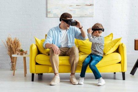 uśmiechnięty ojciec i syn patrząc na siebie siedząc na żółtej kanapie w słuchawkach vr