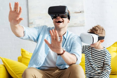excited man gesturing with outstretched hands while using vr headsets together with son