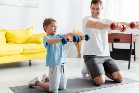 smiling father with son exercising with dumbells while standing on knees on fitness mat