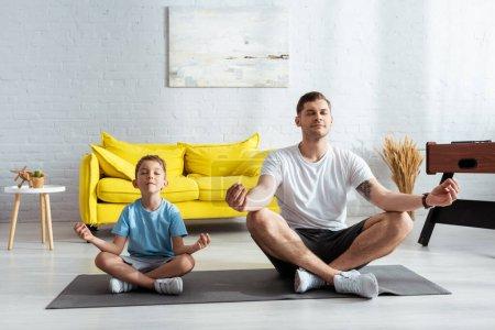 Photo pour Père et fils assis dans des poses de lotus sur tapis de fitness avec les yeux fermés - image libre de droit