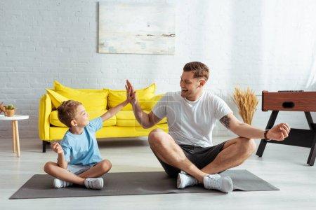 Photo pour Joyeux père et fils donnant haute cinq tout en étant assis sur tapis de remise en forme dans des poses de lotus - image libre de droit