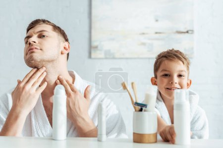 selective focus of serious man touching face near smiling son in bathroom